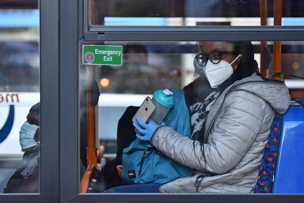 Woman wearing face covering on bus